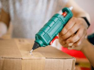 Utilisation pistolet à colle sur carton d'emballage